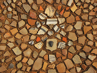 Pottery shards, pottery shards and more pottery shards; with an obsidian arrowhead in the middle.